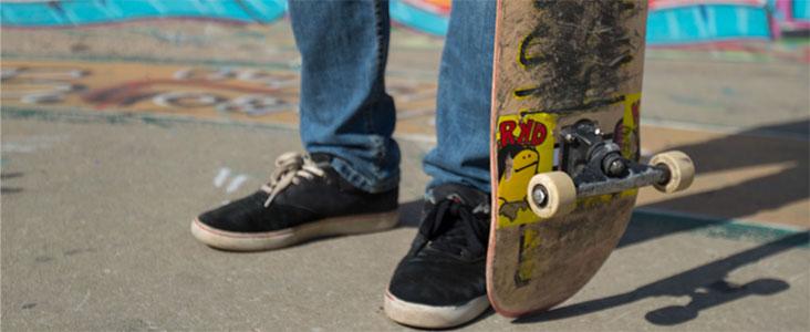 A skateboard beside a persons feet