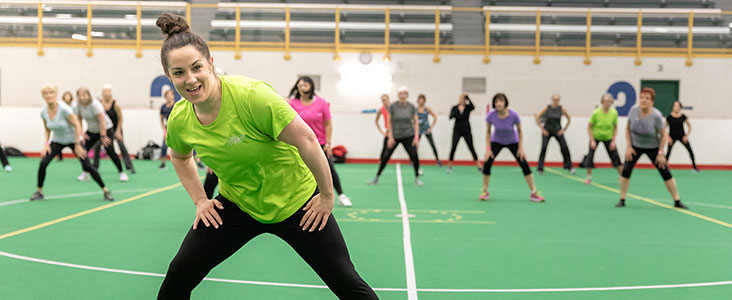 Fitness instructor at Servus Place smiles as she leads a class