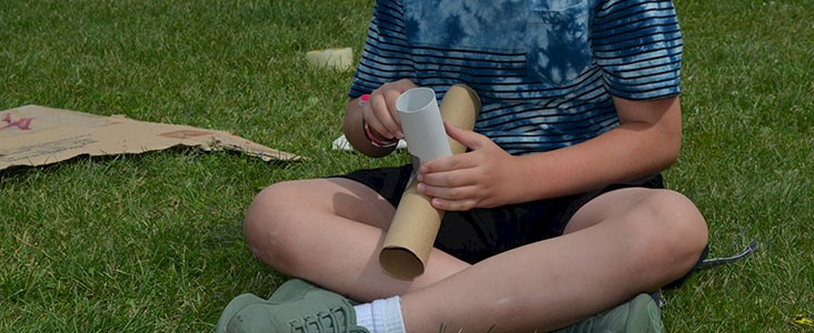 Child plays outdoors on the craft, building a craft