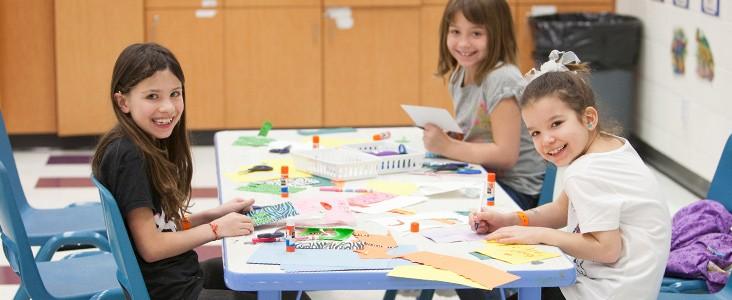 Three children enjoying a craft activity at a table