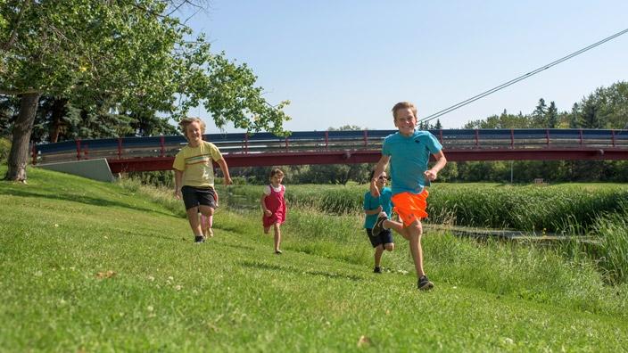 A group of children run through Red Willow Park