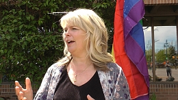 Mayor Heron standing in front of the Pride flag speaking at event