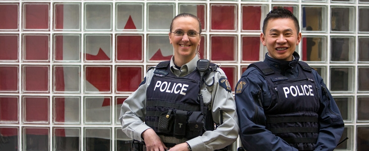 A pair of RCMP officers smiling in front of a Canadian flag