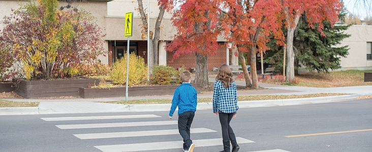 Two children crossing the road