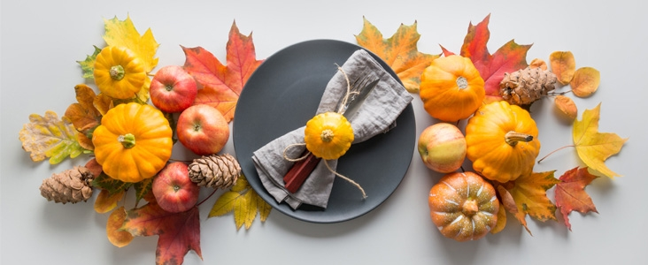 Fall leaves, pumpkins, pine cones and apples surrounding a grey plate and napkin