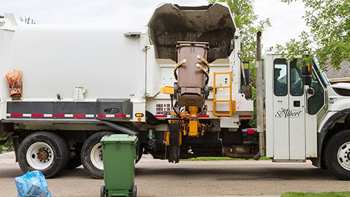 Garbage truck tipping a Brown Garbage Cart into the hopper