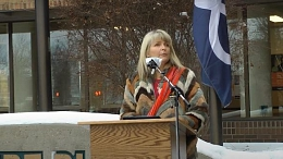 Mayor Cathy Heron standing at a podium reading the proclamation for Metis Week.