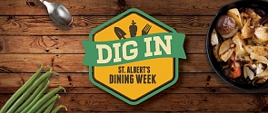 The Dig In logo sitting atop a wooden table with various delicious food items