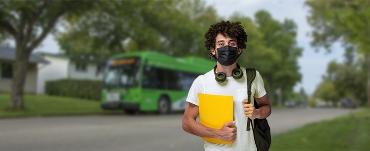Student with a backpack standing in front of a city transit bus