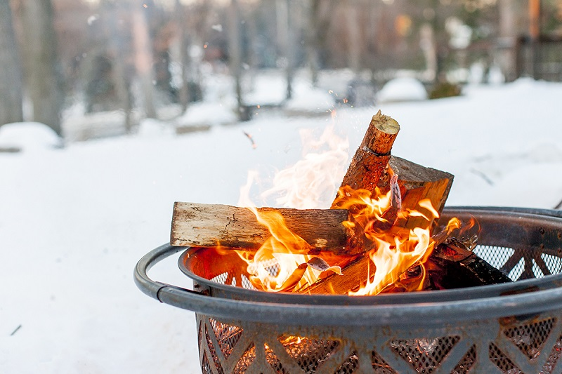 Image of wood burning in a fire pit during the winter.