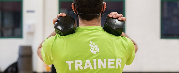 Back of fitness trainer as he teaches a weight class at Servus Credit Union Place