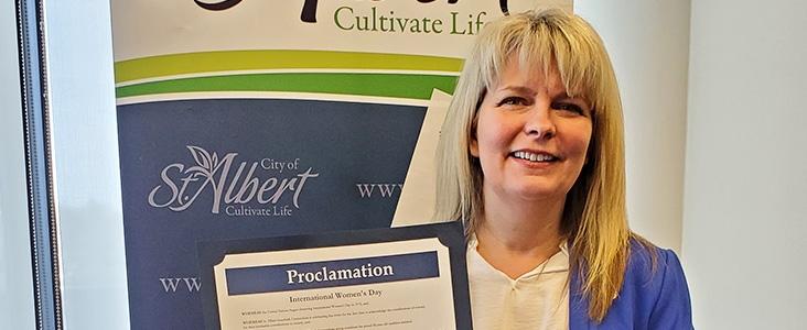 Mayor Cathy Heron holding the International Women's Week Proclamation