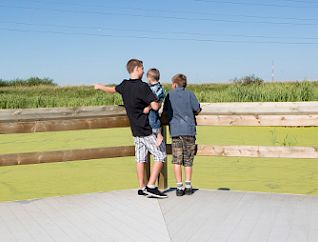 A trio of young boys look over Big Lake from the boardwalk