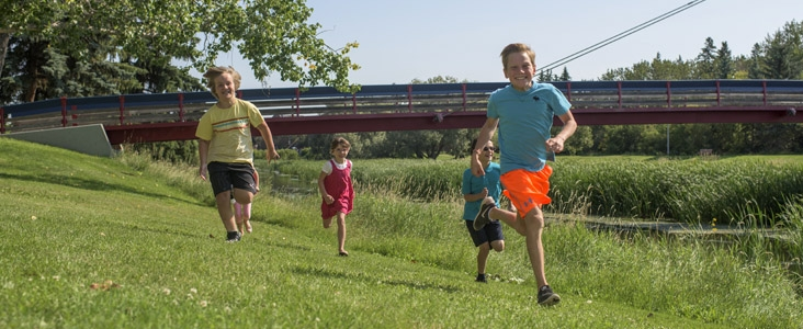 Children run playfully through Red Willow Park near the Children's Brige