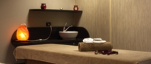 Image of a relaxing massage table setup complete with an orange glowing light and towels.