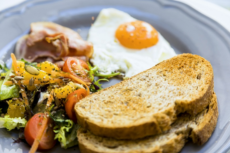 Plate of food including toast, eggs, vegetables and ham.