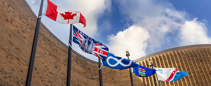 Flags (Canadian, Treaty 6, Metis, Provincial and Municipal) waving out front of St. Albert Place