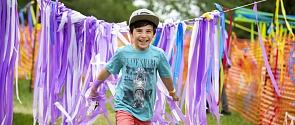 A boy runs through colourful streamers at the Children's Festival