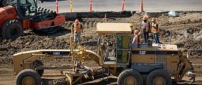 Grader pushing dirt during road construction