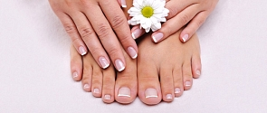 A close-up of a woman's fingers and toes, each with perfect nails. The left hand's holding a daisy.