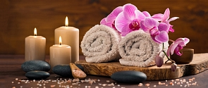 A display with scented candles, pink flowers and clean towels