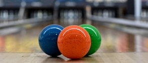 Three bowling balls await their use at the foot of a 5-pin bowling alley.