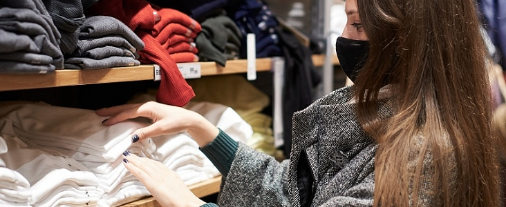 Young woman wearing a mask while shopping for clothes.