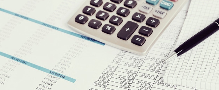 calculator and pen sitting on spreadsheets with numbers