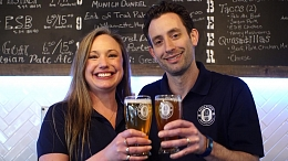 Smiling co-owners of Endeavour Brewing holding branded beer mugs.