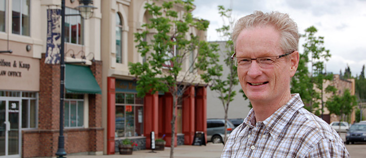 A local businessman stands out front of a row of small businesses