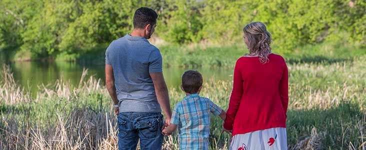 Family standing in front of a river