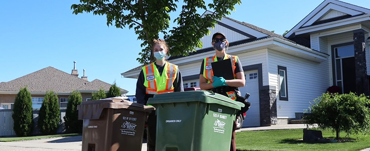 Two workers standing in front of waste and organics carts