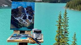 Photo of an artist's canvas on an easel, looking out over a mountain lake. Art by Samantha William-Chapelsky