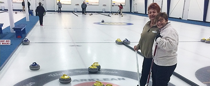 Curlers on curling rink ice holding brooms