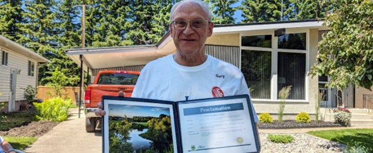 Gary Durie stands on Sonora Drive holding his Good Neighbour Recognition Certificate