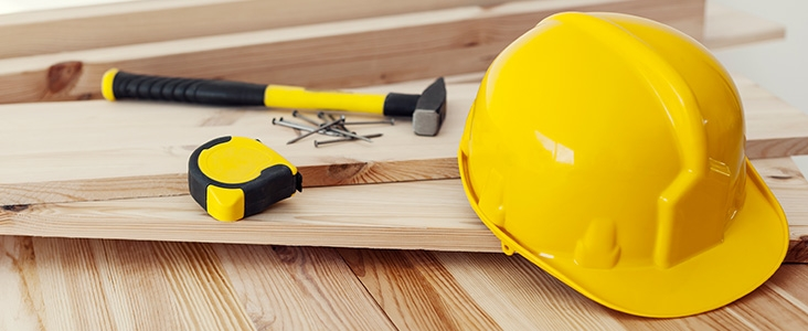 Yellow construction hard hat, tape measure, nails and hammer sitting on pile of wood