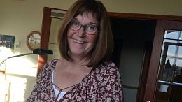 Photo of Colleen Hewitt smiling in her studio.