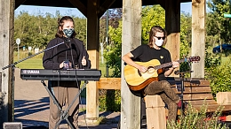 A person playing keyboard and a person playing acoustic guitar outside - Photo Credit Ash Halinda
