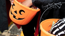 Kids holding Trick or Treat buckets full of candy