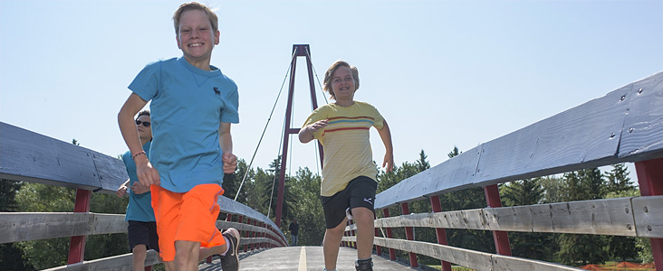 Kids running on Red Willow Trail bridge.