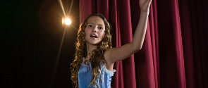 A girl performs a musical number on the Arden Theatre stage