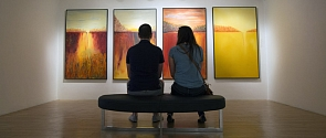 A couple contemplates a quadriptych (a series of 4 paintings) from a bench in the Art Gallery