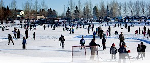 Photo of lots of people skating at a couple of outdoor ice surfaces; one of them has people playing a game of shinny hockey