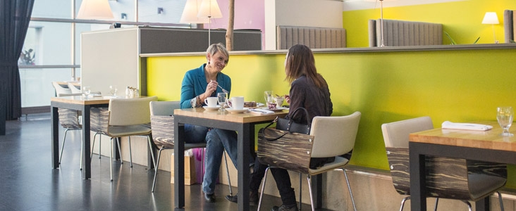 Two women enjoy lunch at the Glasshouse Kitchen within the Enjoy Centre