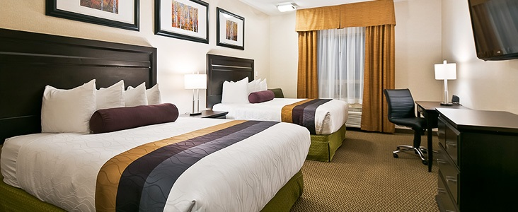 Photo of a Hotel room with two beds, a desk, tv and dresser