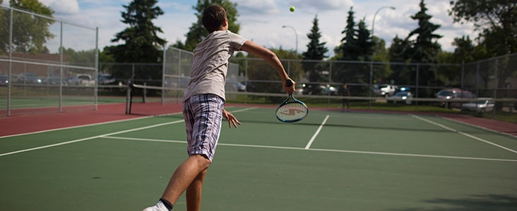 Tennis player serving on the court