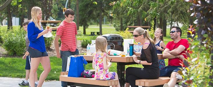 Family having a picnic on a park bench.