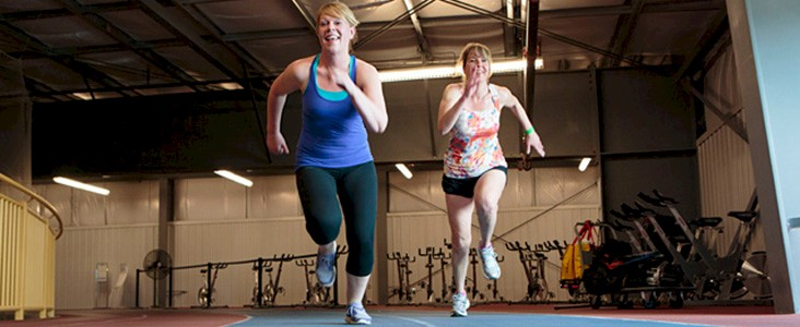 Photo of two women sprinting on the track at Servus Place