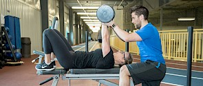 Fitness personal trainer with client lifting weights
