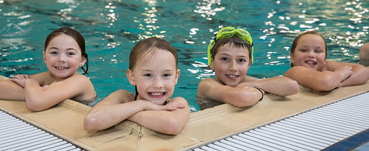 A photo of four kids in the pool leaning against the edge smiling
